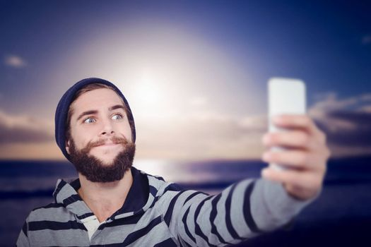 Hipster making face while taking selfie on mobile phone against scenic view of sea against sky