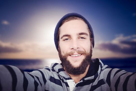 Portrait of happy hipster with hooded shirt against scenic view of sea against sky