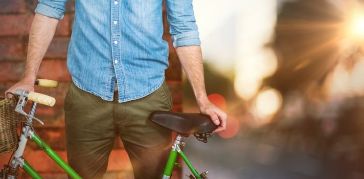Portrait of hipster standing with bicycle against wall of a house