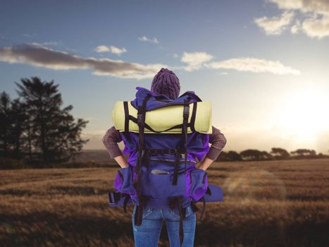 Rear view of a hipster woman with a travel bag against landscape of the countryside