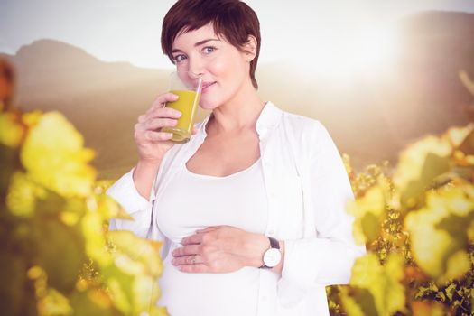 Portrait of happy pregnant woman drinking orange juice against greenness field of grapevine