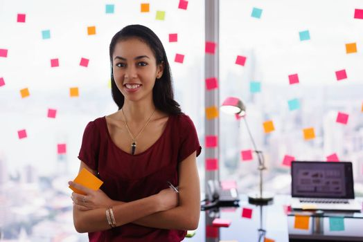 Portrait of proud assistant with arms crossed.The woman stands in office at high floor, against window full of adhesive notes with tasks