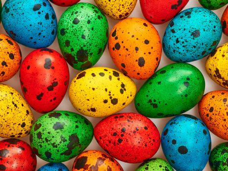 Easter eggs background. Quail eggs hand painted multicolored. Close up. Unusual creative holiday greeting card