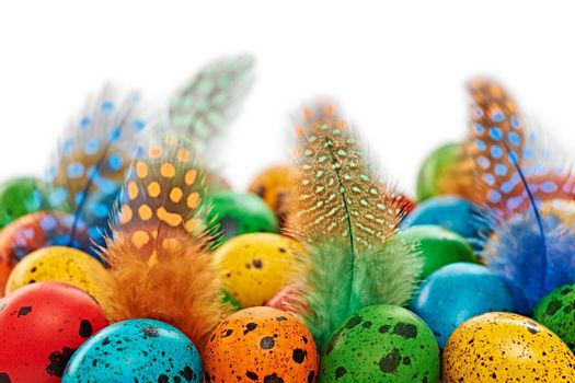 Easter eggs background. Quail eggs hand painted multicolored, and feathers. Close up. Unusual creative holiday greeting card