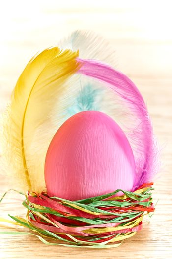Easter egg in nest. HHand painted decorated egg with and feathers on wooden background. Unusual creative holiday greeting card