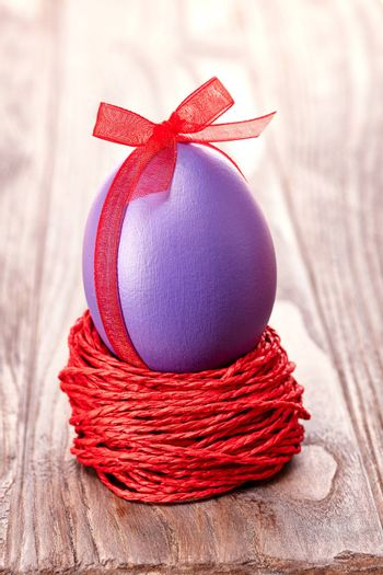 Easter egg in nest. Hand painted decorated egg with bow on wooden background. Unusual creative holiday greeting card