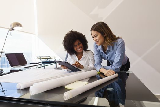 Two architects in modern office building, sitting on desk with blueprints and housing projects. The women hold a tablet and surf the web. They smile and talk each other.