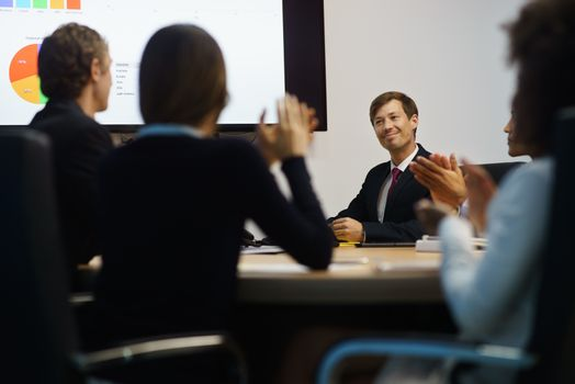 Group of business people meeting in corporate conference room, applauding at a coworker during his presentation. The man is showing charts and slides on a big TV monitor