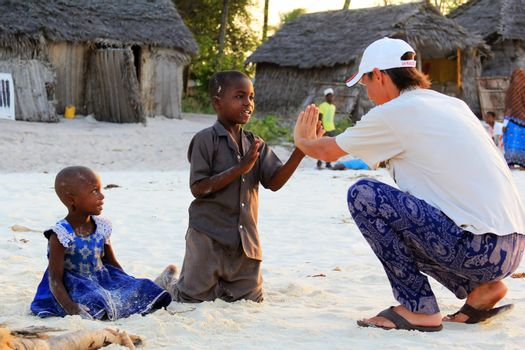 Zanzibar, Tanzania - January 9, 2016: Adult man tourist plays with African children on the beach in the village of Nungwi in Zanzibar, Tanzania
