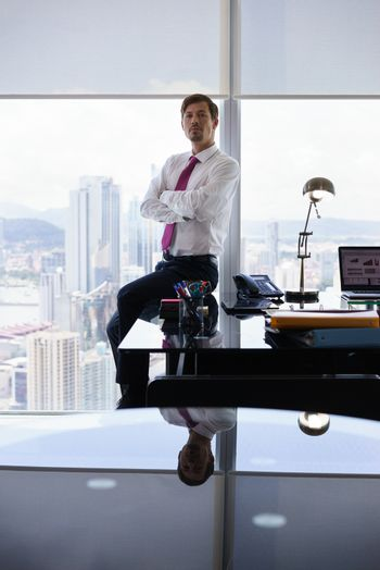 Adult businessman sitting in modern office with sight of the city. The man looks at camera with serious expression and arms crossed