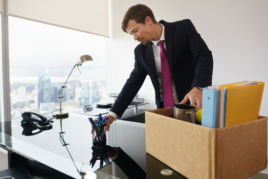 Businessman recently hired for corporate job moves into his new executive office with a view of the city. He takes office supplies out of a box and arranges his things on desk