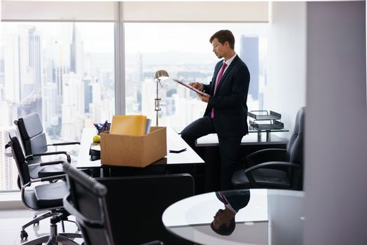 Businessman recently hired for corporate job moves into his new office. He takes out a folder from a box and reads documents near a big window, with a view of the city.