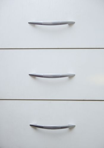 Cabinet with sliding trays and chrome handles. Close-up