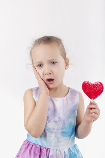 Toothache. Little girl with lollypop and hurt teeth holding her cheek.