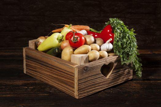 Organic seasonal vegetable in rustic wooden crate. Healthy vegetable eating.