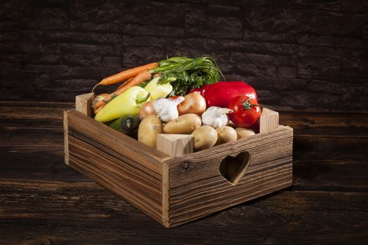 Organic seasonal vegetable in rustic wooden crate. Healthy vegetable eating.