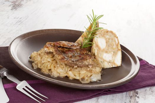 Baked pork chop with dumplings and sauerkraut on plate with silver cutlery on wooden table.