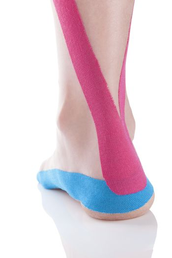 Kinesio tape on female heel isolated on white background. Chronic pain, alternative medicine. Rehabilitation and physiotherapy.