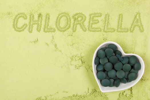 Green food supplement. Word chlorella written in green ground powder, top view. Healthy lifestyle.
