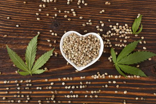 Hemp seeds on wooden background, top view. Cannabis and hemp.