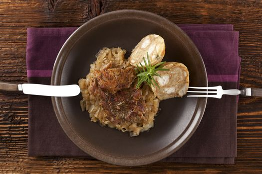 Baked pork chop with dumplings and sauerkraut on plate with silver cutlery on wooden table, top view.