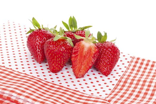 Delicious ripe strawberries on red and white dotted background. Healthy fruit eating.