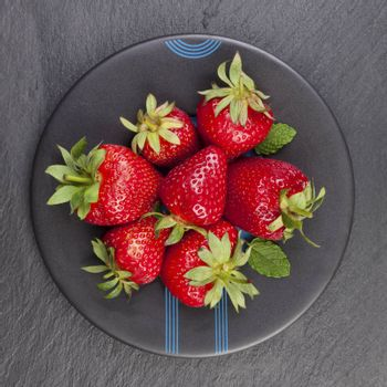 Delicious ripe strawberries on black plate on black stone, flat lay. Healthy fruit eating.