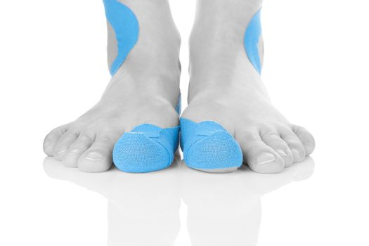 Kinesio tape on female foot isolated on white background. Chronic pain, alternative medicine. Rehabilitation and physiotherapy.