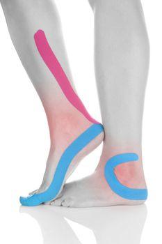 Kinesio tape on female leg isolated on white background. Chronic pain, alternative medicine. Rehabilitation and physiotherapy.