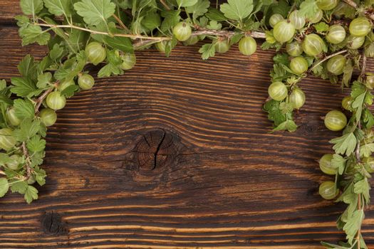 Green gooseberries with green leaves on wooden vintage table, top view. Healthy summer fruit eating.