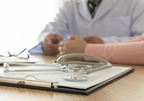 stethoscope and medical documentation  with doctor and patient background