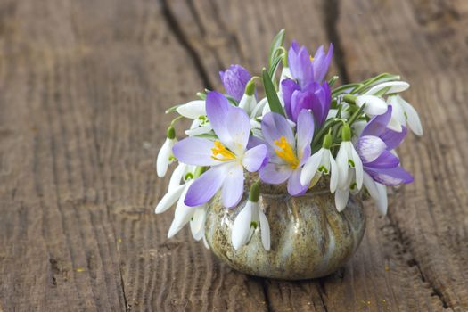 Bunch of crocus and snowdrops in a vase on the wooden table.