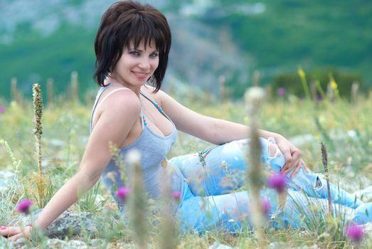 Pretty young woman on the field with green grass