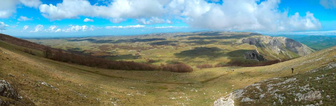 Panorama. Hills with cloudscape and blue sky.