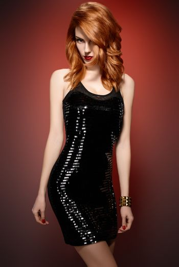 Fashion portrait of sexy beauty woman in stylish sequins dress. Unusual creative provocative. Emotional playful redhead glamour girl, luxury accessories, evening elegant party style on red, people
