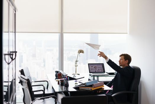 Corporate manager in modern office takes a break and prepares a paper airplane. The bored man dreams of his next vacations and leans back on his chair. Copy space