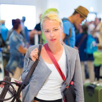 Female traveller waiting in airport terminal.