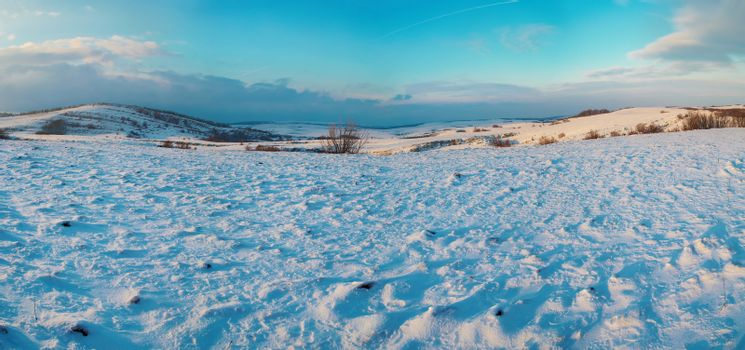Panorama with winter hills covered by snow against sunset