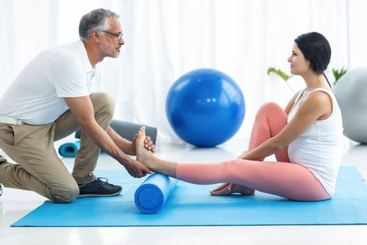 Doctor examining and giving physiotherapy to pregnant woman on exercise ball