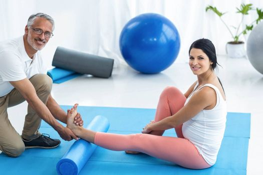 Portrait of doctor examining and giving physiotherapy to pregnant woman on exercise ball