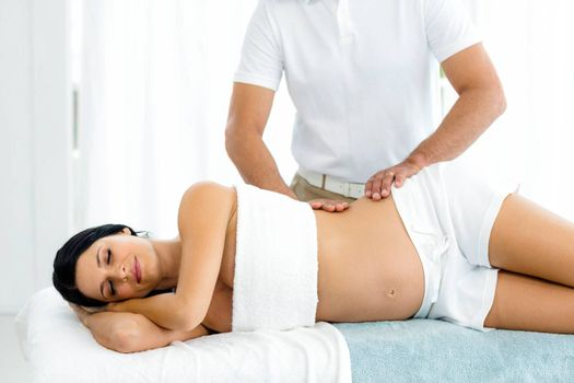Pregnant woman receiving a back massage from masseur at home