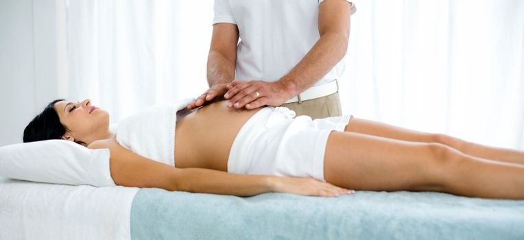Pregnant woman receiving a stomach massage from masseur at home