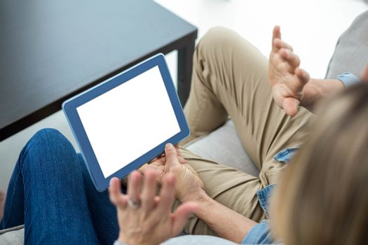 Couple sitting on sofa and using digital tablet
