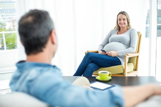 Pregnant woman sitting on chair and using smartphone