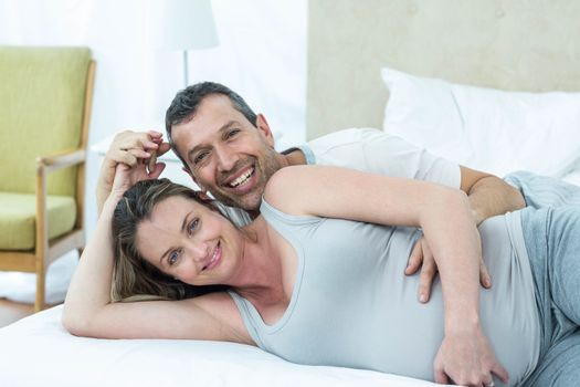 Expecting couple lying on bed