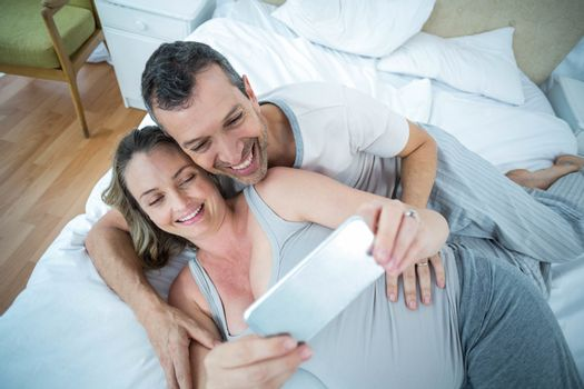 Expecting couple lying on bed and using digital tablet