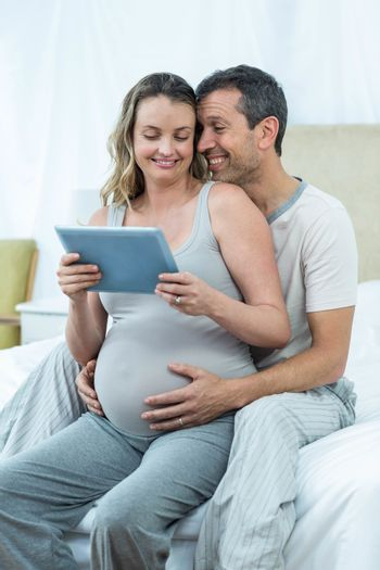 Expecting couple sitting on bed and using digital tablet