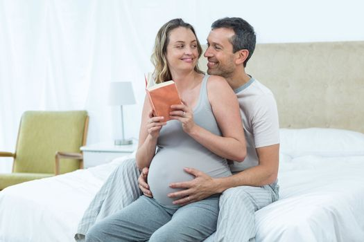 Expecting couple sitting on bed