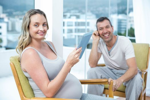 Expecting couple sitting on chair and using digital tablet