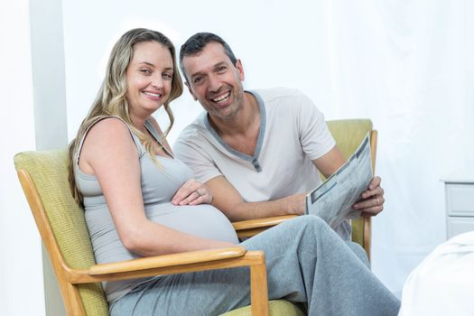 Expecting couple sitting on chair